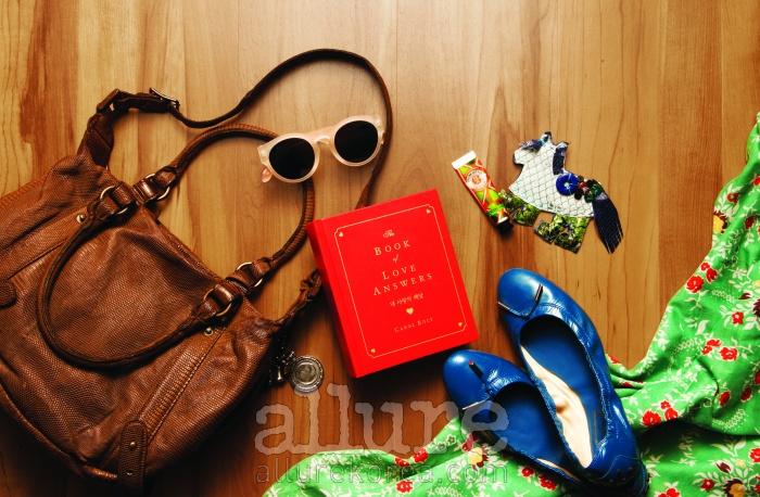 (왼쪽부터) 가죽 숄더백은 크리스티앙 포(Christian Peau).선글라스는 그라픽 플라스틱(Grafik Plastic). 지혜를 담은 책. 립밤은 록시땅(Loccitane). 뱀피소재의 말 모양 브로치는 이태원 로드숍 '가루'에서 구입한 것.발레리나 슈즈는 토즈(Tod's). 꽃무늬 패브릭은 맑은 날 나무그늘아래서 한가로운 시간을 보내기 위한 용도.