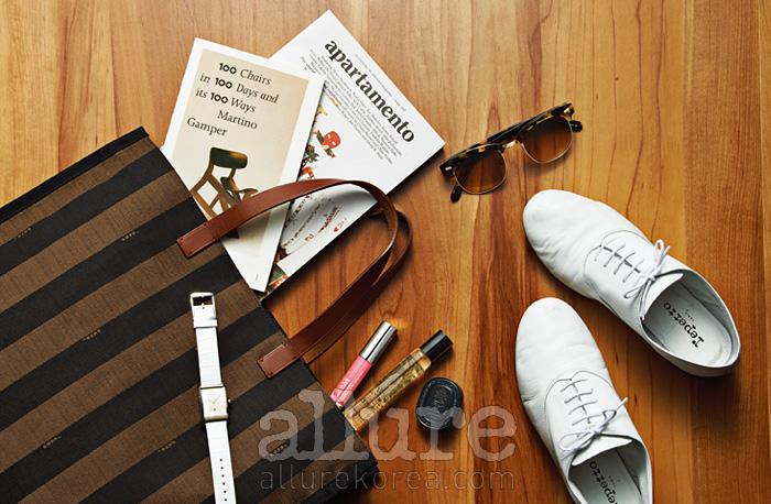 (왼쪽부터) 쇼퍼백은 펜디(Fendi). 시계는 ck 워치(ck Watch).의자에 관한 아트북 . 라이프스타일 매거진 . 컬러립밤은 크리니크(Clinique). 향수는 모두 딥티크(Diptyque).선글라스는 블랙 아이웨어(Black Eyewear). 옥스퍼드 슈즈는레페토(Repetto).
