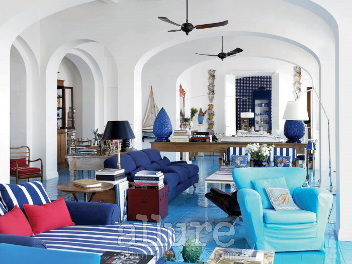 흰색 벽과 푸른색 타일, 푸른색 소파가 조화를 이루는 실내 전경
