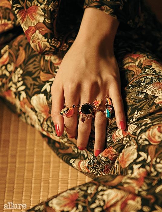 검지에 낀 스톤 장식의 골드 도금 소재 반지, 중지에 낀 인조 다이아몬드 장식의 골드 도금 소재 반지, 약지에 낀 스톤 장식의 골드 도금 소재 반지 모두 레 네레이드(Les Nereides).