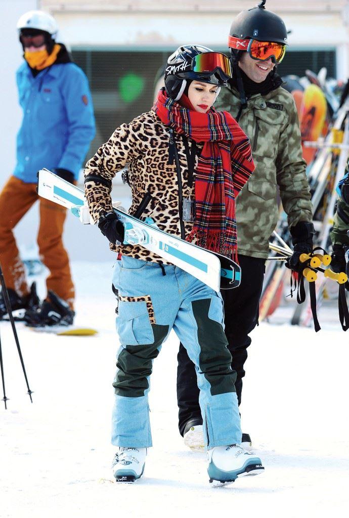 그웬 스테파니 강렬한 호피무늬 재킷에 레드 타탄 체크 머플러와 블루 팬츠를 매치한 그녀의 대담한 스키 룩.