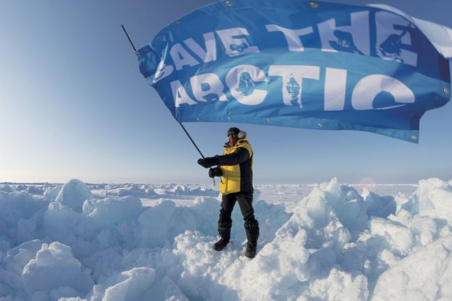 Renny Bijoux from the Seychelles, an Arctic ambassador with the North Pole expedition team,  waves a 'Save the Arctic' banner upon arrival at the North Pole.  He is part of a team who has brought a time capsule containing 2.7 million names of supporters who wish to protect the Arctic. They plan to lower the capsule and a 'flag for the future' to the seabed beneath the North Pole.
