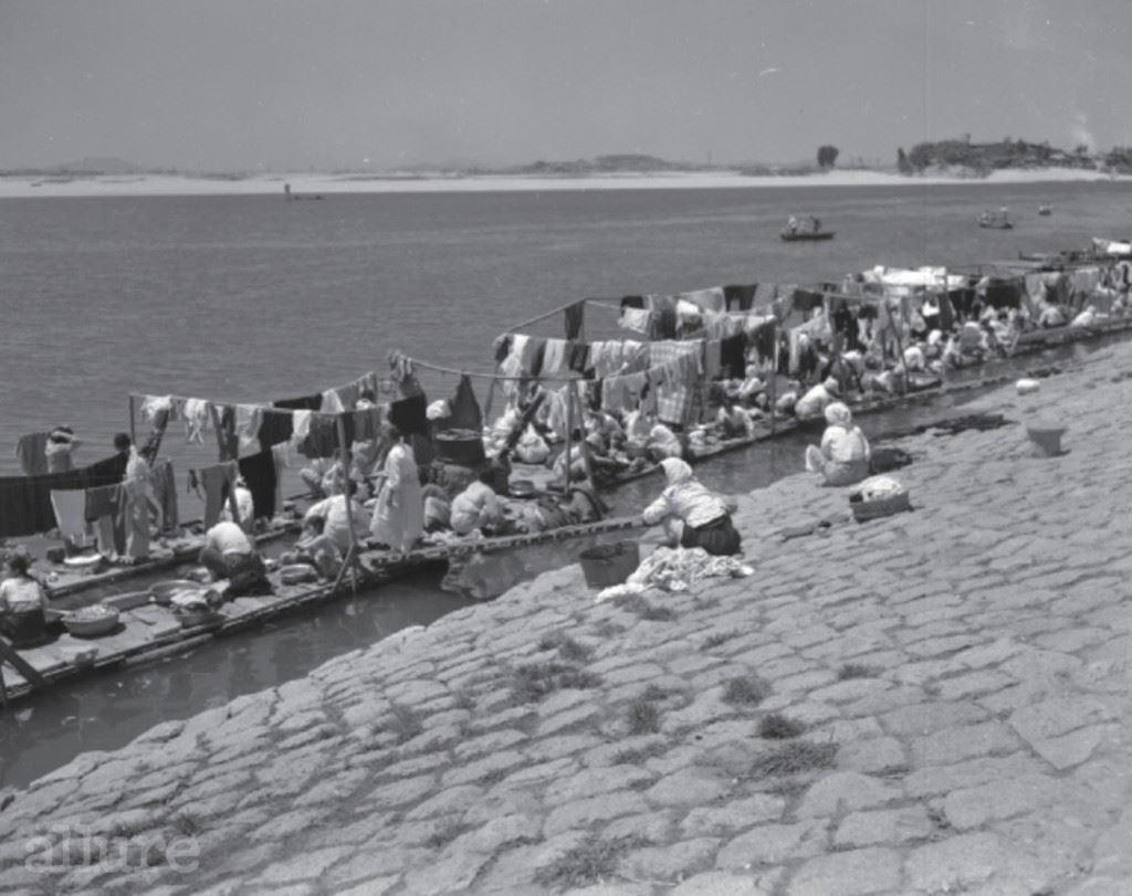 마 포 강 변 빨 래 터, 1 9 6 2 현재의 마포대교 북쪽에 자리했던 마포나루는 한강의 4대 나루터 중 하나로 상인들의 집결지였다. 역시 한강을 따라 형성된 마포 강변의 빨래터는 당시 전차 종점 근처의 수문 가까이에 위치해 있었다. 수도 사정이 좋지 않은 탓에 각자의 가정에서 빨랫감을 이고 가서 빨래를 했던 것이다. 1960년대 초반까지만 해도 한복을 입는 이들이 많아서 빨래를 삶는 것이 필수였는데, 소형선박 바지선에 돈을 내고 빨래를 삶곤 했다.