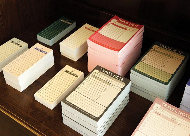 가게 내부의 나무 책상에는 판매 중인 포스터 카드와 메모지 등이 놓여 있다.