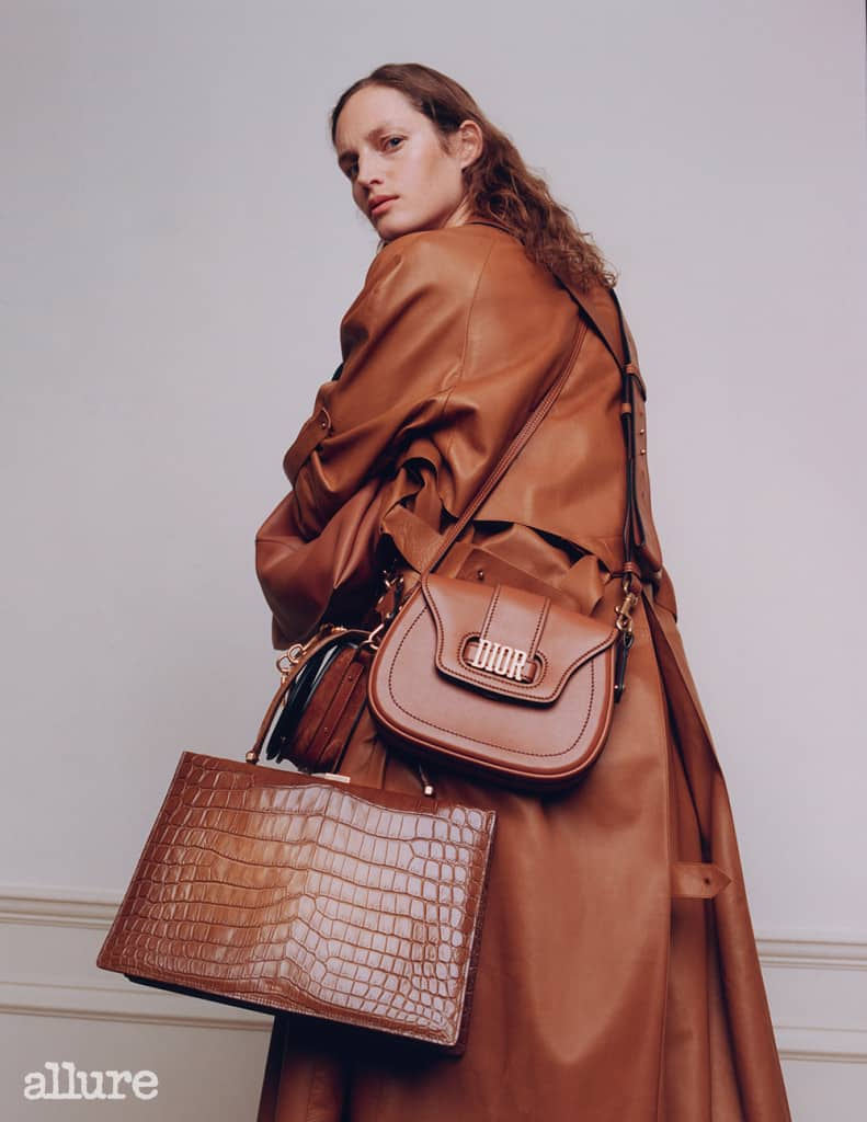 Feature, accessories, classic, heirloom, neutral palette, model, curly hair, natural look, turning, shows back, wears leather trench coat, selection of brown bags