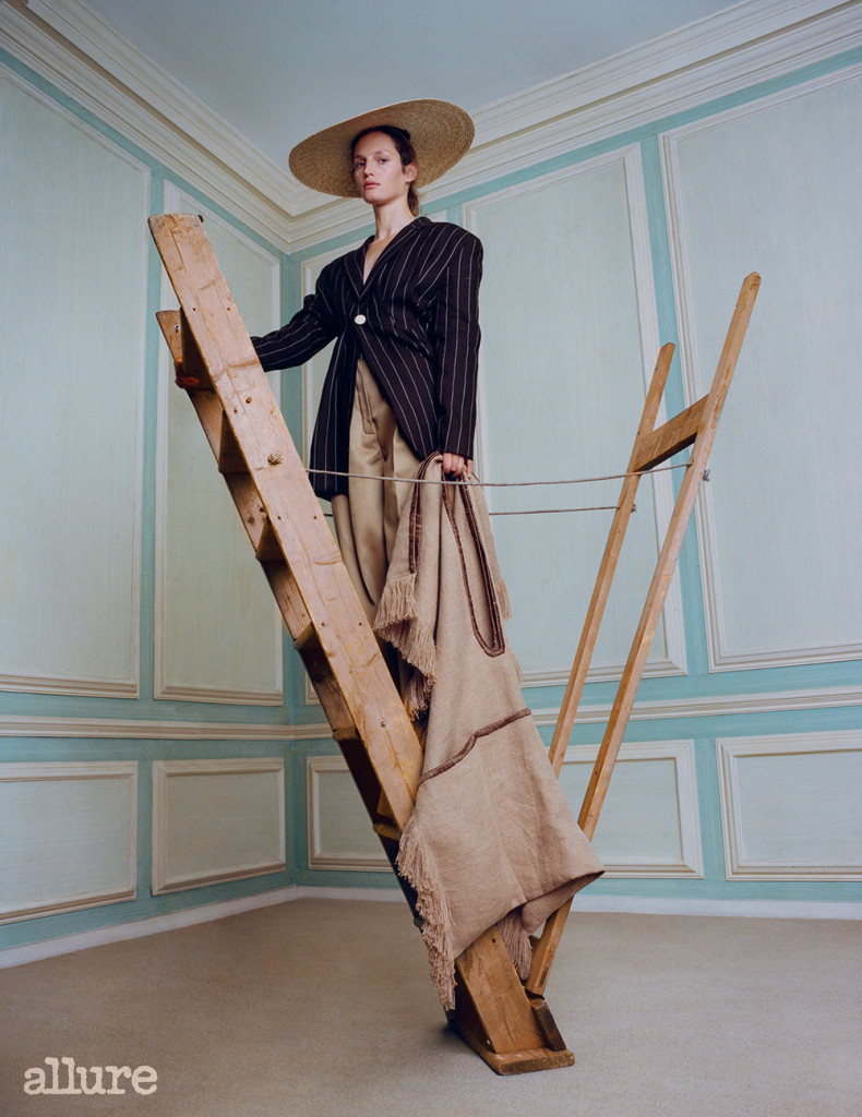 Feature, accessories, classic, heirloom, neutral palette, model, curly hair, natural look, standing on upside-down ladder, holds oversized jute bag, wears striped wool blazer, straw hat, beige trousers
