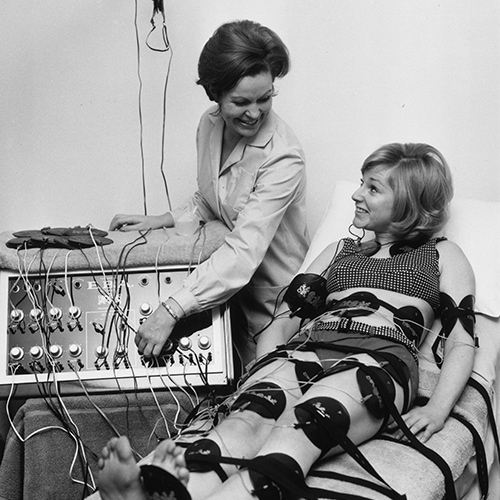 29th January 1968:  Paula Byrne demonstrates an electronic slimming device to actress Alison Frazer. Pads all over Alison's body stimulate her muscles with a mild electric current, with the same result as exercise.  (Photo by Keystone/Getty Images)
