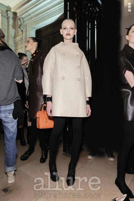 둥그스름한 형태감과 동그란 단추 장식, 손목을 드러내는 소매 등 60년대 실루엣이 가죽 소재와 만나면 그 형태감은 더욱 위풍당당해진다.