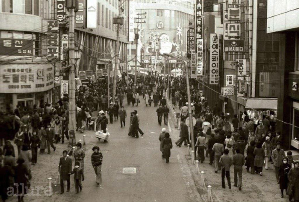 명 동, 1 9 7 6 크리스마스를 일주일 앞둔 1976년 12월 18일 촬영된 명동의 풍경. 일제강점기 당시 일본인들이 '혼마치'라고 부르며 도쿄의 긴자에 맞먹는 상가로 개발한 명동 일대는 그 시대에도 의상실과 다방을 찾아 나선 멋쟁이로 가득했다. 1970년대 중반의 명동 역시 장발족은 물론 하루 최대 100만 명이 모여드는 번화가 그 자체였다. 사진 정면에 보이는 것은 당시 미도파 백화점으로 1939년에 조지아 백화점이라는 이름으로 지어진 것이다. 이후 롯데그룹이 인수하면서 2002년 롯데 영플라자로 개관했다. 왼편으로는 당시 종로 YMCA와 함께 단골 데이트 장소였던 코스모스 백화점의 간판이 희미하게 보인다.
