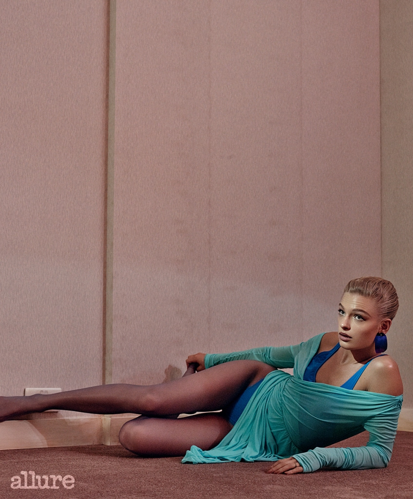 Fashion feature, blue, sport-inspired, room, model, short sleek hair, thick lashes, floor, wall, wears turquoise wrap dress, swimsuit, tights, earring