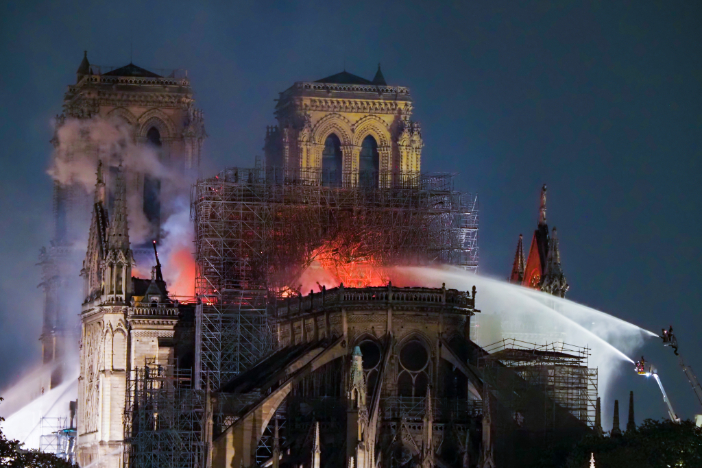 Firefighters work to extinguish the fire outside famed Notre-Dame Cathedral on April 15, 2019 in Paris, France.  A massive fire is ripping through the cathedral in central Paris, toppling the spire on the 850-year-old Gothic monument and leaving France in shock over the potential loss of one of the nation's most famous landmarks. The cause is unknown but officials said it was possibly linked to ongoing renovation work. Pictured: Notre-Dame de Paris Ref: SPL5080268 150419 NON-EXCLUSIVE Picture by: SplashNews.com Splash News and Pictures Los Angeles: 310-821-2666 New York: 212-619-2666 London: 0207 644 7656 Milan: 02 4399 8577 photodesk@splashnews.com World Rights, No Belgium Rights, No France Rights, No Switzerland Rights